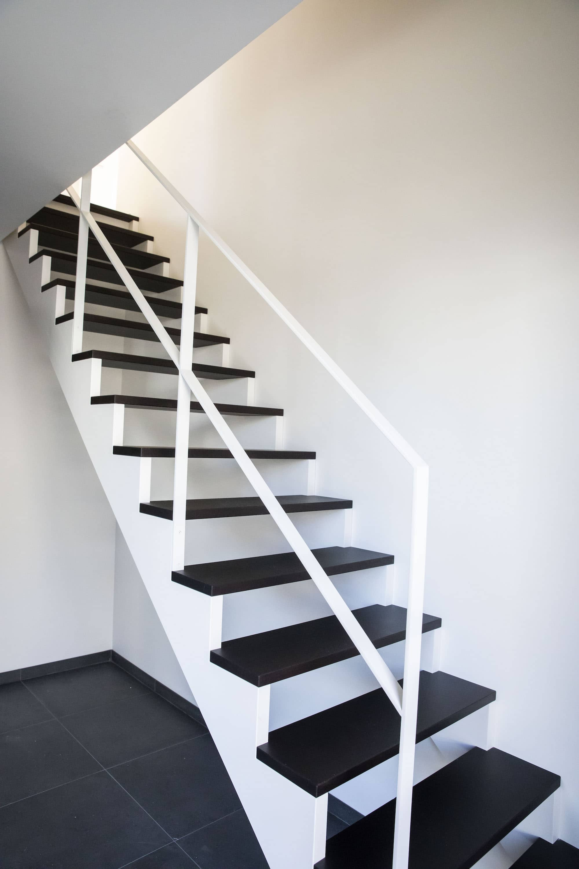 Open Z-trap met gelakte metalen leuning. Tredes in Franse eik, overige delen zijn gelakt