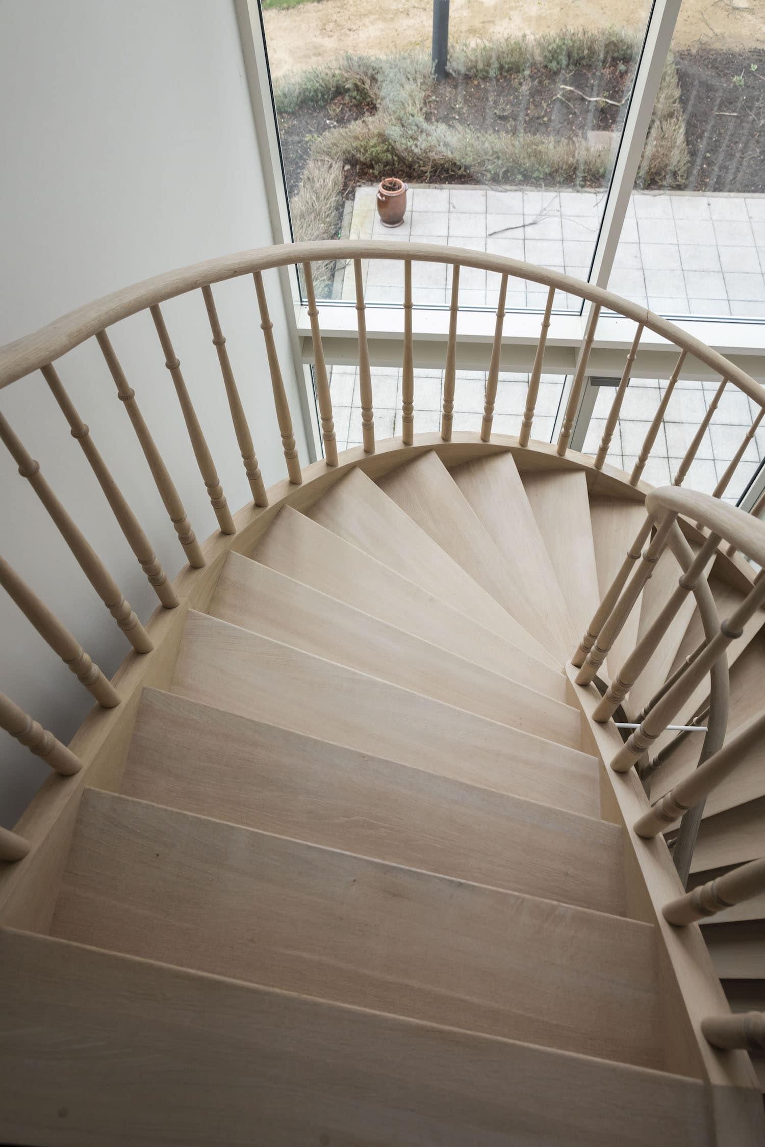 Traditionele gesloten trap in Franse eik - tredes volledig verdreven - met gedraaide beginpaal en balusters, met ronde bloktrede en wrongstuk
