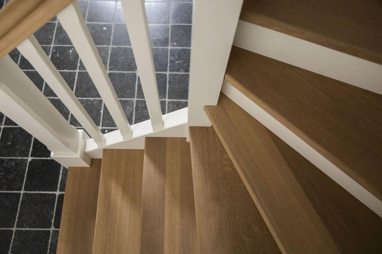 Traditionele gesloten trap met leuning model Cottage. Tredes en handgreep in Franse eik, overige delen zijn gelakt